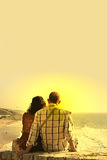 Couple seated watch the sunset Stock Photos