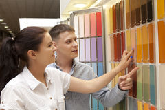 Couple select paint color and look matching samples at household Stock Photos