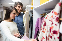 Couple selecting a dress while shopping for clothes. In apparel shop Stock Images