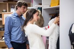 Couple selecting a dress while shopping for clothes Royalty Free Stock Photos