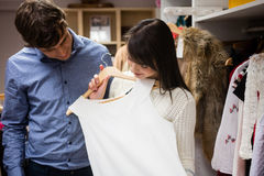 Couple selecting a dress while shopping for clothes Stock Image