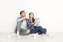 Couple selecting furniture online for new apartment. While sitting on floor in empty living room, white background Stock Photography