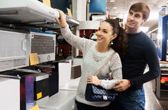 Couple selecting kitchen hood. Newly married couple selecting kitchen hood in hypermarket and smiling royalty free stock photography