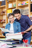 Couple Selecting Papers Together In Store Stock Image
