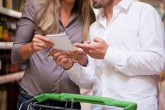 Couple Selecting Products at Supermarket Stock Photos