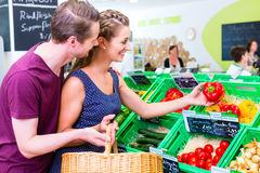 Couple selecting vegetables in corner shop Stock Image