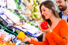 Couple selecting vegetables in hypermarket Stock Images