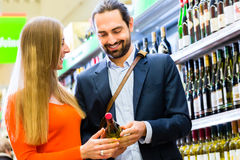 Couple selecting wine in market Stock Photo