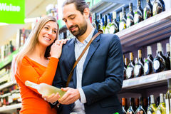 Couple selecting wine in supermarket Royalty Free Stock Image