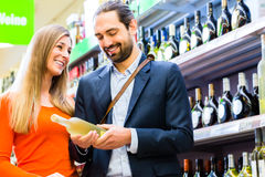 Couple selecting wine in supermarket Stock Photo