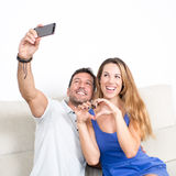 Couple selfie while woman making a heart Royalty Free Stock Photo