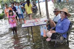 A couple is selling lottery tickets in a flooded street of Bangkok, Thailand, on 31 October 2011 stock photography