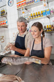 Couple selling a white salmon Royalty Free Stock Images
