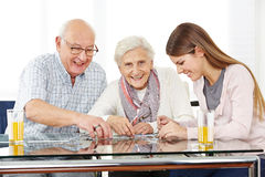 Couple senior citizens playing. With a jigsaw puzzle with her granddaughter royalty free stock photography