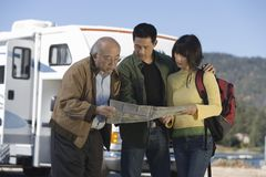 Couple and senior father reading map outside RV. Couple and senior father reading map RV in background Royalty Free Stock Photos