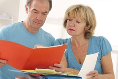 Couple of senior looking at administrative and financial document Stock Images