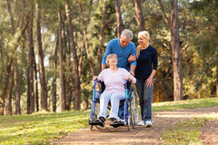 Couple senior mother. Caring couple taking their disable senior mother for a walk at the park royalty free stock photos