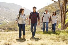 Couple and senior parents talking during a mountain walk stock photo