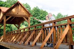 Couple of senior personalities standing on big wooden bridge. Wooden bridge. Couple of senior personalities wearing jeans and white shirt standing on big wooden stock image