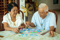 Couple senior playing with a jigsaw puzzle at home. Asian couple senior playing with a jigsaw puzzle at home stock images