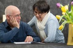 Couple of senior reading a book at home. A couple of senior reading a book at home royalty free stock photos