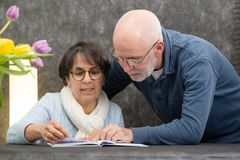 Couple of senior reading a book at home. A couple of senior reading a book at home stock image