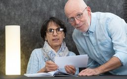 Couple of senior reading mail at home. A couple of senior reading mail at home royalty free stock photos