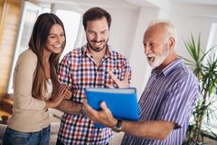 Couple with senior real-estate agent visiting house for sale stock photography