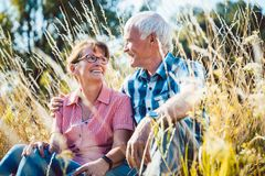 Couple of senior woman and man sitting in a meadow in the grass. Couple of senior women and men sitting in a meadow in the grass looking at each other stock photography