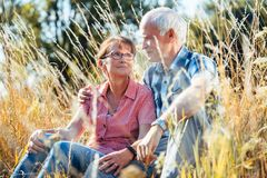 Couple of senior woman and man sitting in a meadow in the grass. Couple of senior women and men sitting in a meadow in the grass looking at each other royalty free stock photography