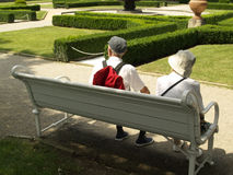A couple of seniors. Sitting on a bench in the park - Praha - summer day Stock Image