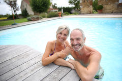 Couple of seniors enjoying swimming pool stock images