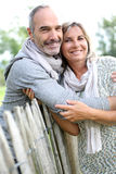 Couple of seniors leaning on wood fence Royalty Free Stock Image