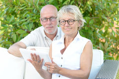 A couple of seniors look at a digital tablet Stock Images