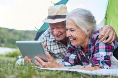 Couple of seniors using tablet computer while camping. Happy couple seniors camping with tablet computer at campsite stock photo