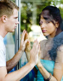 Couple separated by glass royalty free stock image