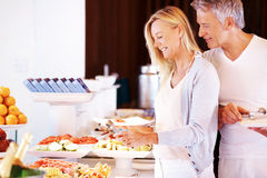 Couple serving food at buffet Stock Images