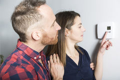 Couple set the thermostat at home. A couple set the thermostat at home Royalty Free Stock Image