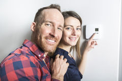 Couple set the thermostat at home. A couple set the thermostat at home Stock Photo