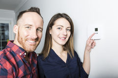 Couple set the thermostat at home. A couple set the thermostat at home Royalty Free Stock Photo