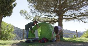Couple setting tent under trees. Young people putting up tent at place of rest under trees while hiking in mountains in summer stock footage
