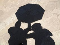 Couple Shade with Umbrella. Projected on the concrete floor stock photos