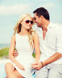 Couple in shades at seaside Stock Photo