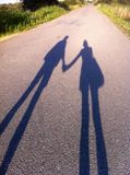 Couple shadows. Sunset longway together holding hands royalty free stock photos