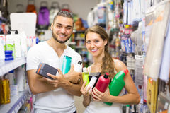 Couple with shampoo in the store. Happy young couple buying detergents, shampoo and perfume in supermarket Stock Photos