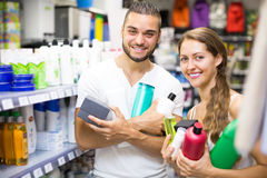 Couple with shampoo in the store. Happy young couple in good spirits with detergents, shampoo and perfume  in the store Stock Photos