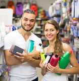 Couple with shampoo in the store. Happy young smiling couple buying detergents, shampoo and perfume in supermarket Stock Image