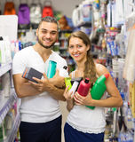 Couple with shampoo in the store. Young couple buying detergents, shampoo and perfume in supermarket Stock Image