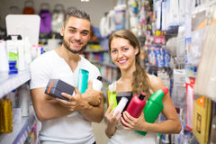 Couple with shampoo in the store. Young smiling couple buying detergents, shampoo and perfume in supermarket Stock Photography