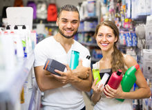 Couple with shampoo in the store. Young smiling couple in good spirits with detergents, shampoo and perfume  in the store Stock Photography